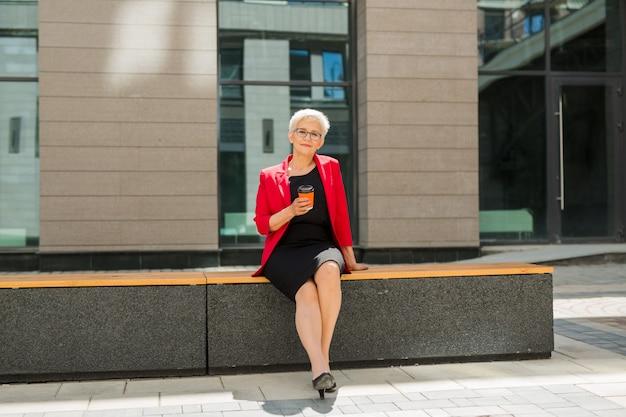 Bella donna anziana in età con un taglio di capelli corto e occhiali in una giacca rossa con una tazza di caffè