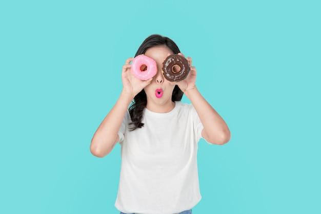 Bella donna asiatica allegra che la copre occhi di ciambelle variopinte su fondo blu.