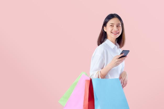 Bella donna asiatica allegra che tiene i multi sacchetti della spesa colorati con lo smartphone su fondo rosa-chiaro.