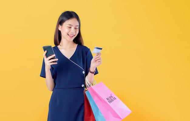 Bella donna asiatica allegra che tiene i multi sacchetti della spesa e carta di credito colorati con lo smartphone su arancione-chiaro.