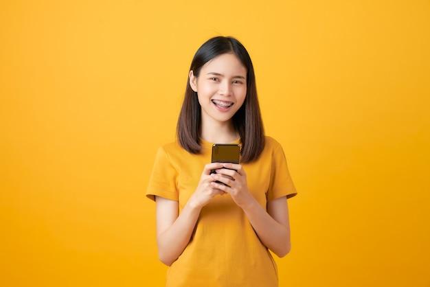 Bella donna asiatica allegra che tiene uno smartphone