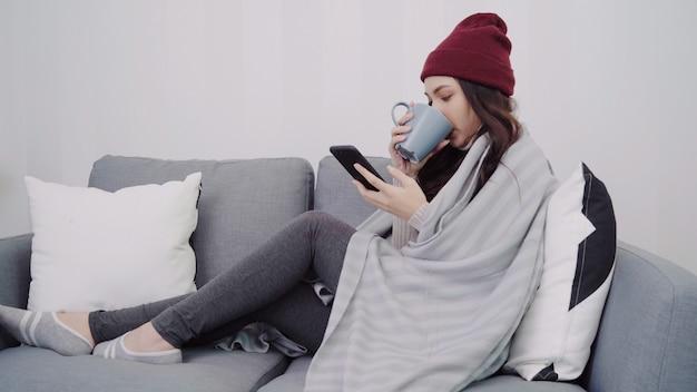Bella donna asiatica attraente utilizzando smartphone per l'invio di messaggi e la lettura