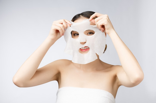 Bella donna asiatica che applica la maschera dello strato di carta sul suo fondo di bianco del fronte