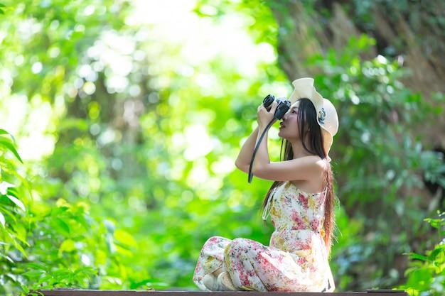 Bella donna asiatica che cattura foto nel parco