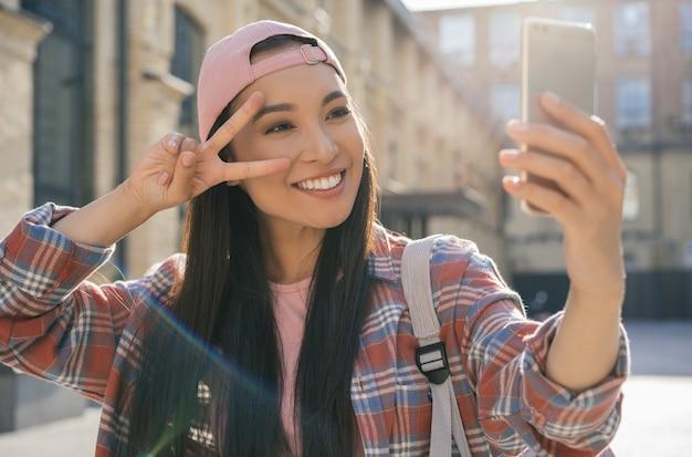 Bella donna asiatica che cattura selfie, mostrando il segno di vittoria