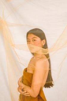 Bella donna asiatica che esamina la macchina fotografica