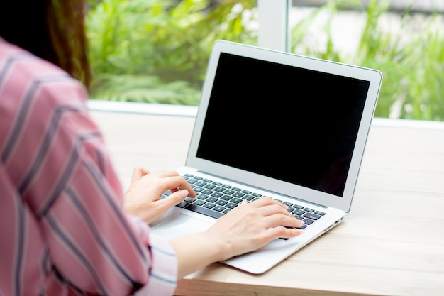 Bella donna asiatica che lavora online sul computer portatile