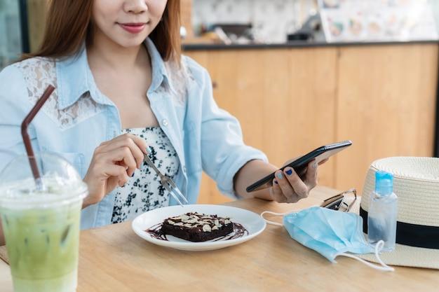Bella donna asiatica che mangia torta brownie durante l'utilizzo di smart phone nella caffetteria.