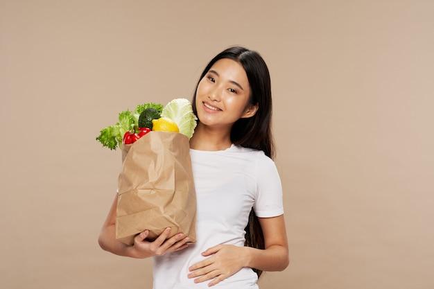 Bella donna asiatica che posa con la borsa delle verdure
