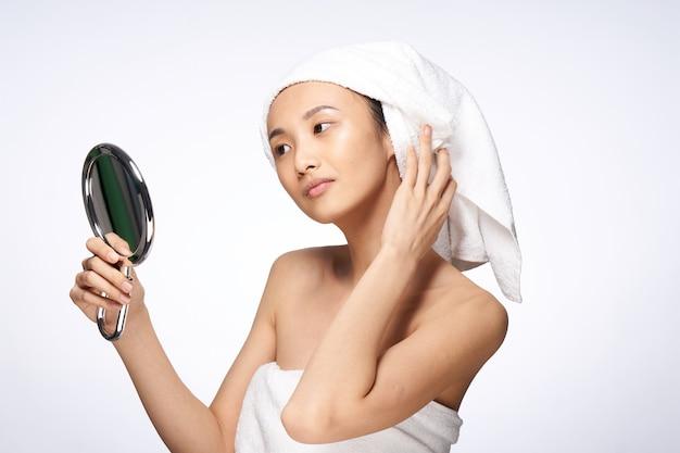 Bella donna asiatica che prende cura della sua pelle isolata