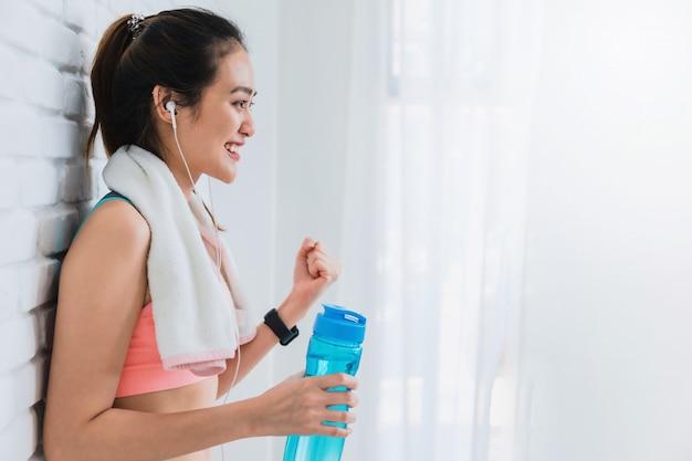 Bella donna asiatica che riposa e che tiene bottiglia di acqua dopo yoga ed esercizio del gioco sul fondo bianco del muro di mattoni.