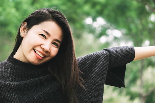 Bella donna asiatica che sorride alla macchina fotografica con la natura all'aperto