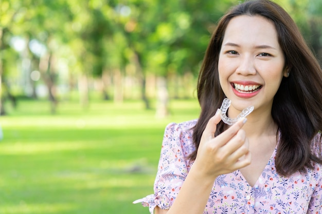 Bella donna asiatica che sorride con la mano che tiene fermo del dispositivo di allineamento dentale al parco naturale all'aperto
