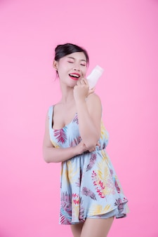 Bella donna asiatica che tiene una bottiglia di prodotto su uno sfondo rosa.