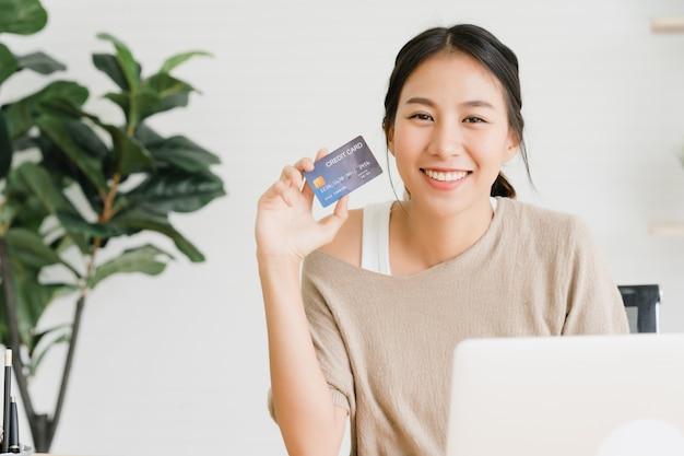 Bella donna asiatica che utilizza computer o computer portatile che compra lo shopping online
