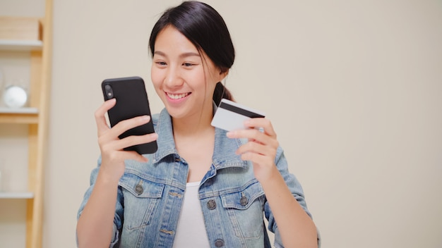 Bella donna asiatica che utilizza smartphone che compra acquisto online dalla carta di credito mentre usura seduta casuale sullo scrittorio in salone a casa.