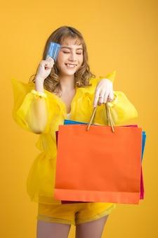 Bella donna asiatica con il sacchetto della spesa e la carta di credito a disposizione