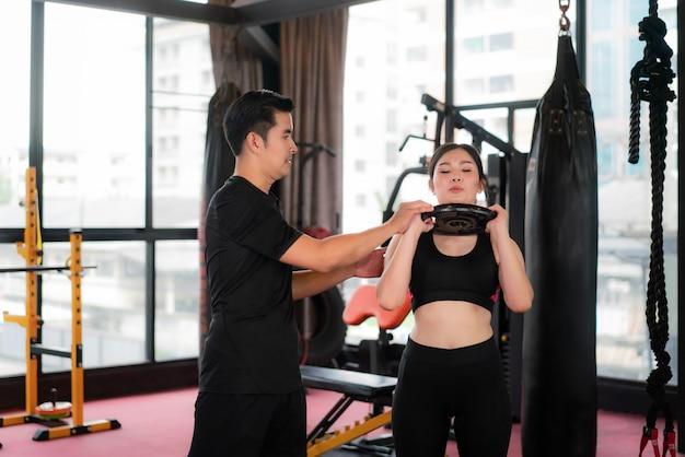 Bella donna asiatica di sport in palestra con l'esercizio della ginnastica di potenza con peso e personal trainer fitness pratica per lei. vestibilità sportiva per stile di vita sano modello asiatico del concetto di palestra di boxe.