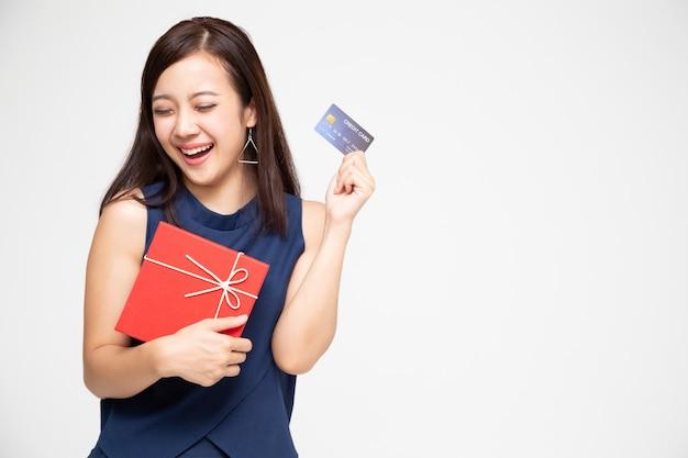 Bella donna asiatica felice che giudica il contenitore di regalo rosso e la carta di credito a disposizione isolati