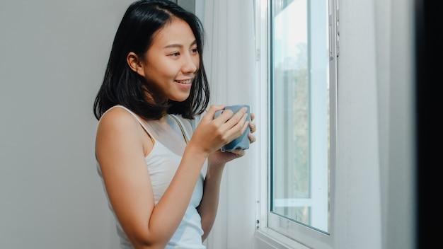 Bella donna asiatica felice che sorride e che beve una tazza di caffè o un tè vicino alla finestra in camera da letto. le tende aperte della giovane ragazza latina e si rilassano nella mattina. stile di vita signora a casa.