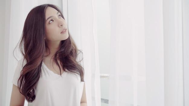 Bella donna asiatica felice che sorride e che beve una tazza di caffè o un tè vicino alla finestra nella camera da letto.