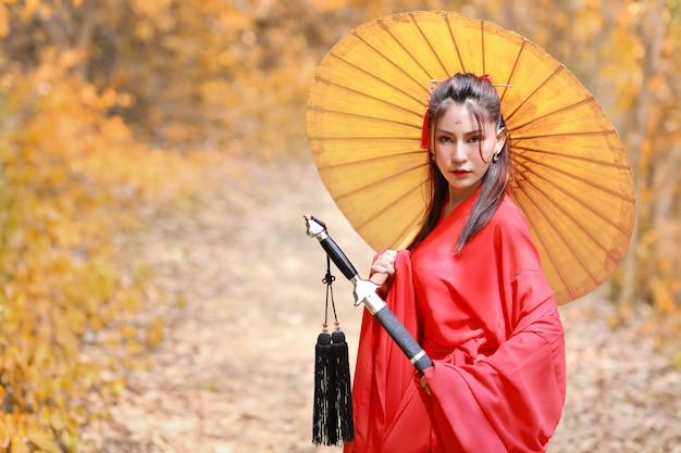 Bella donna asiatica in costume cinese rosso con l'ombrello antico e la spada antica nera con pacifica
