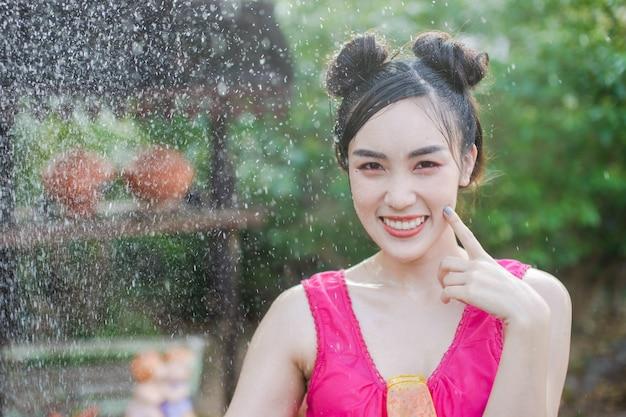 Bella donna asiatica in costume tradizionale della tailandia che gioca acqua in festiva di songkran