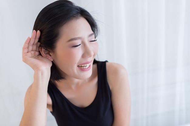 Bella donna asiatica in maglia nera ritratto con azione di felicità