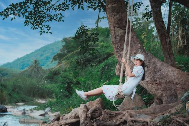 Bella donna asiatica in un'altalena al fiume