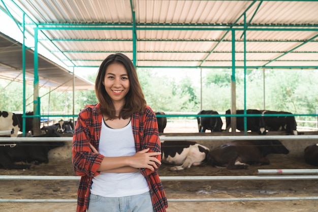 Bella donna asiatica o agricoltore con e mucche in stalla in azienda lattiero-casearia