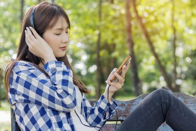 Bella donna asiatica seduta ascoltando musica
