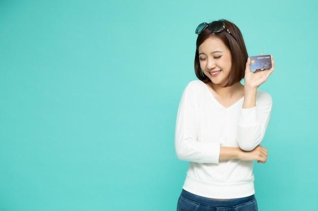 Bella donna asiatica sorridente dei giovani che presenta la carta di credito