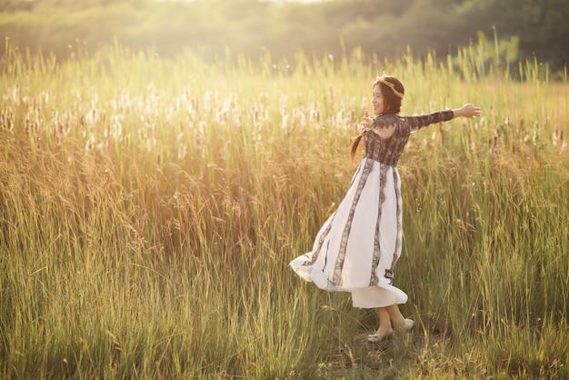 Bella donna asiatica spensierata nei campi che sono felici all'aperto. di libertà e divertimento.