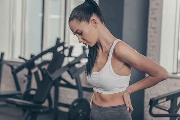 Bella donna atletica che ha mal di schiena dopo l'allenamento in palestra