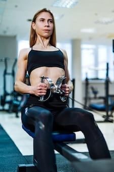 Bella donna atletica che si esercita sul vogatore in palestra leggera.