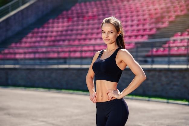 Bella donna atletica con corpo in forma in abiti sportivi neri sta riposando dopo l'allenamento