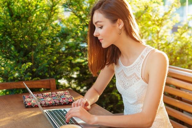 Bella donna attraente al caffè con un computer portatile con una pausa caffè