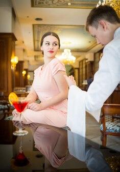 Bella donna attraente in abito da sera facendo un ordine