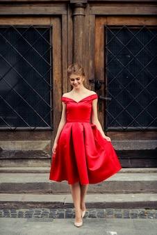 Bella donna attraente in vestito rosso nella città sopra la vecchia porta d'annata
