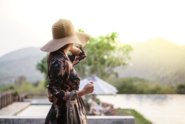 Bella donna attraente sulla terrazza della piscina con cappello oversize sugli occhi