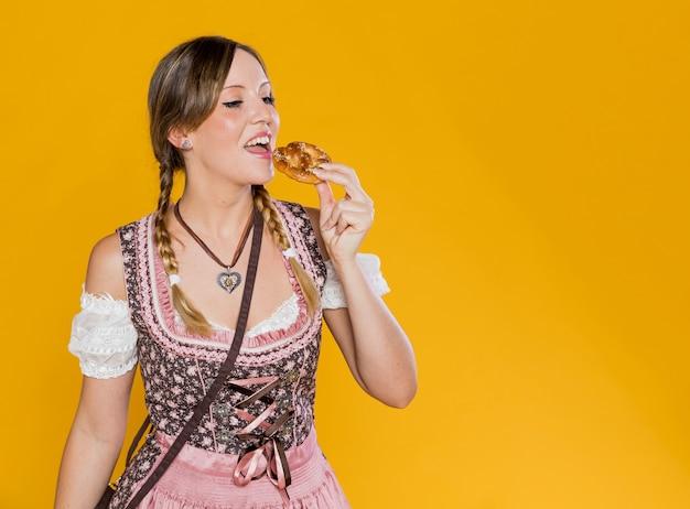 Bella donna bavarese che mangia ciambellina salata