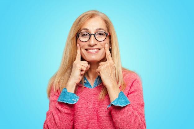 Bella donna bionda adulta costringendo un sorriso sul viso con entrambi gli indici, come se l'invio di un