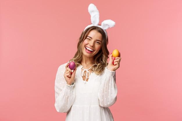 Bella donna bionda allegra che celebra il giorno di pasqua in orecchie di coniglio
