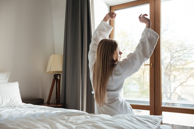 Bella donna bionda che allunga le mani al mattino