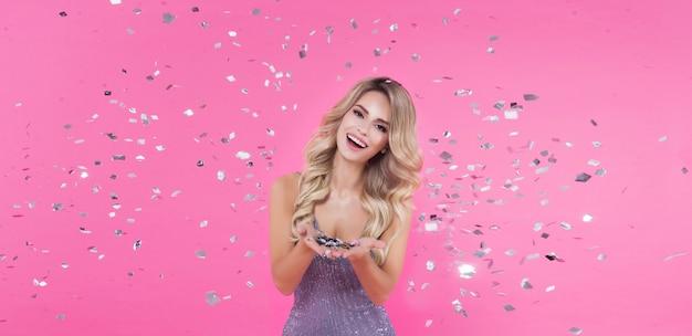 Bella donna bionda che celebra i coriandoli di lancio della festa di buon compleanno o del nuovo anno sul rosa