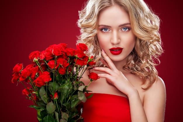 Bella donna bionda che tiene il mazzo di rose rosse