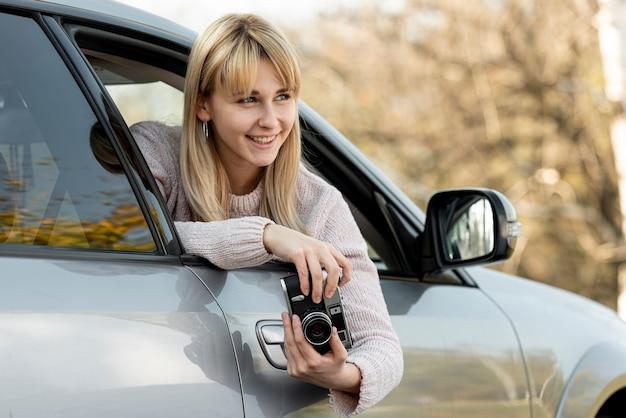 Bella donna bionda che tiene una macchina fotografica d'epoca