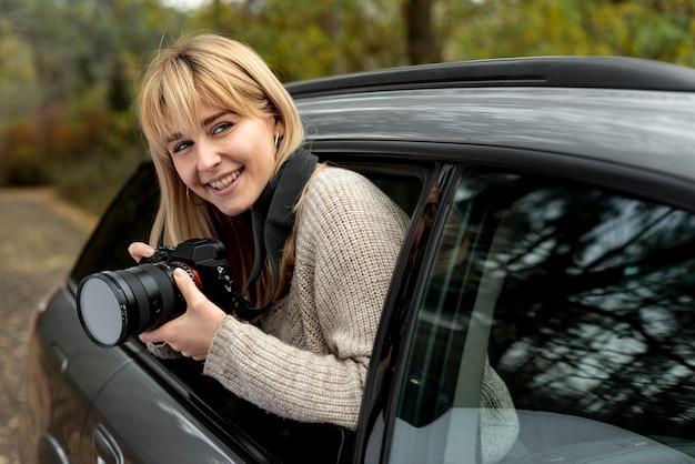 Bella donna bionda che tiene una macchina fotografica professionale