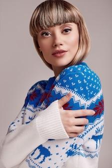 Bella donna bionda con i capelli corti in maglione di natale