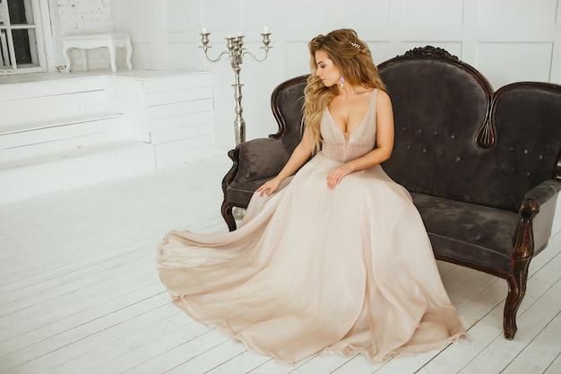 Bella donna bionda con l'acconciatura greca in abito da sposa atlante polveroso beige che posa nella stanza dello studio
